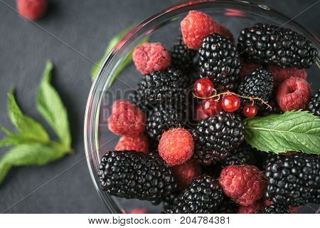Top view photo of a glass plate with ripe red blackberries raspberries and green mint leaves on a black surface. Macro photo of ripe blackberries and raspberries.