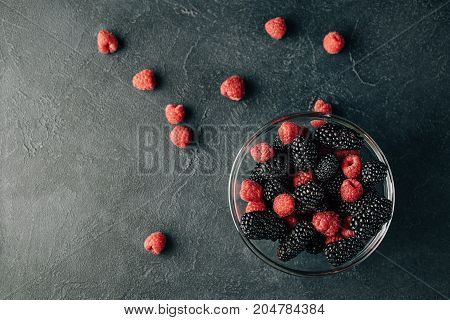 Top view photo of a glass plate with ripe red blackberries and raspberries on a black surface. Macro photo of ripe blackberries and raspberries. Berries scattered of a surface.