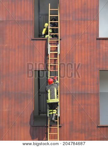 firefighters during a long ladder exercise and the fire brigade building
