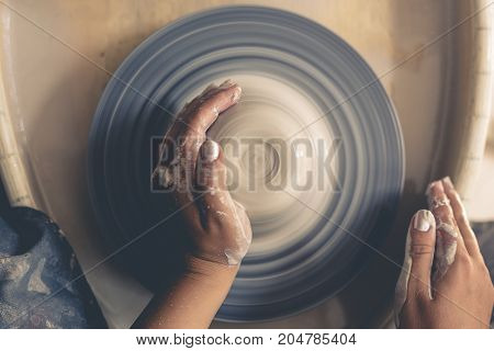 Woman potter hands working on pottery wheel, top view, toned