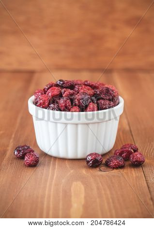 Dried cranberries in white bowl on wooden background