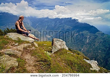 Man sits on mountain peak and looks down on the Kullu valley. Naggar, India - August 2017. Himachal Pradesh. North India.