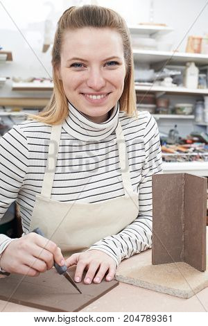 Portrait Of Young Woman Making Pot in Ceramics Studio
