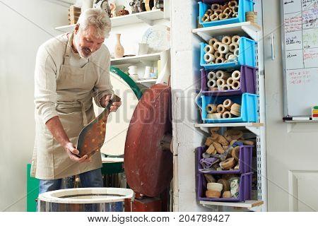 Mature Man In Pottery Studio Firing Vase In Kiln