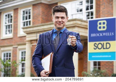 Male Realtor Standing Outside Residential Property Holding Keys