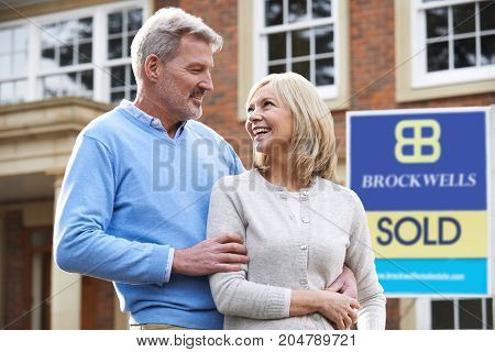 Happy Mature Couple Standing Outside House With Sold Sign