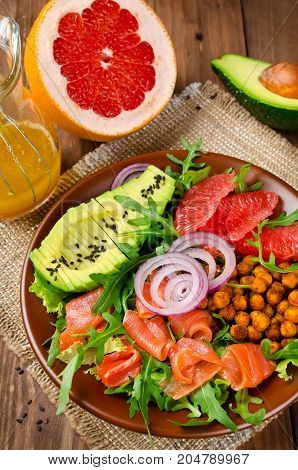 Healthy salad bowl with salmon grapefruit spicy chickpeas avocado red onion and arugula. Delicious balanced food concept