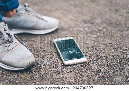 woman dropped mobile phone on the ground and smashed the screen, picking it up