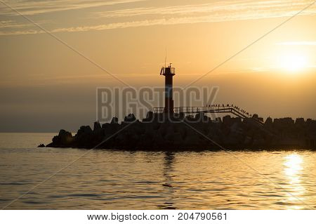 marine sunset with a view of the navigation light and the silhouettes of cormorants