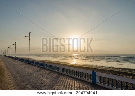 Atlantic beach promenade with stone walkway during sunset at Sidi Ifni, Morocco, North Africa.