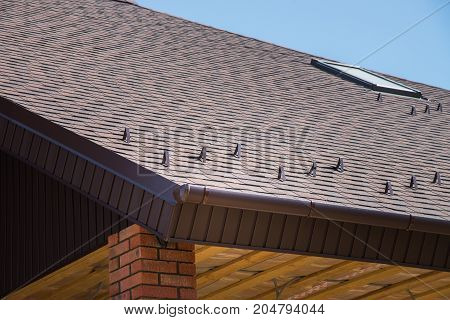Tiled brown roof of new house with overflow, protection, from snow and fronton made of siding.