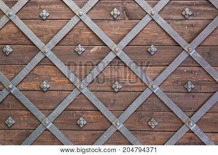Old medieval castle door texture with faded wood and metal