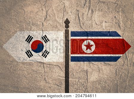 Image relative to politic situation between South Korea and North Korea. National flags on destination arrow road. Grunge distress texture.