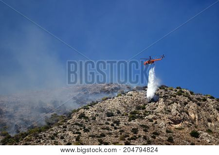 Fire helicopter extinguishes the fire on the hillside . Greece.