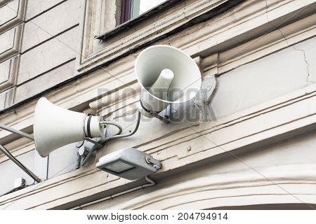 Warning citizens by loudspeakers on the wall. White megaphones on old building