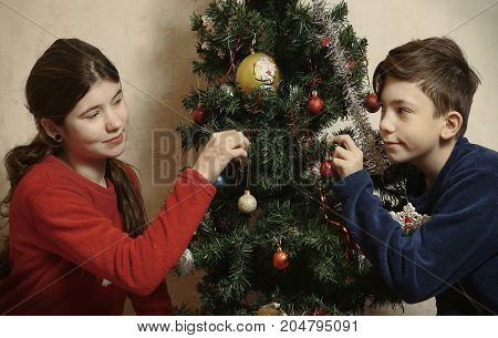 Teenager Girl And Boy Decorating Christmas Tree