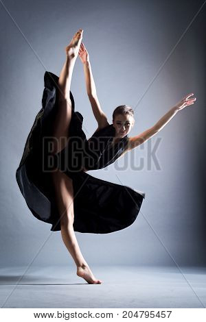 A beautiful athletic girl in a black dress is dancing. In the jump.