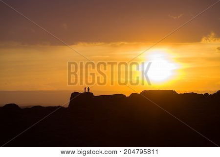 Two people standing on a distant mountain ridge silhouetted by a large setting sun just above the horizon in the Gobi Desert of Mongolia