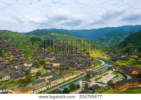 High angle view of the river and mountains behind the traditional wooden houses of Xijiang Miao ethnic minority village in Guizhou China