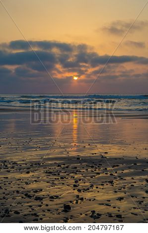 Beautiful atmospheric sunset at beach with reflections and plack pebbles, coast at Sidi Ifni, Morocco, North Africa.