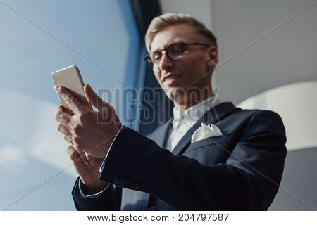 From below shot of smiling man in suit and glasses browsing smartphone in office near window.