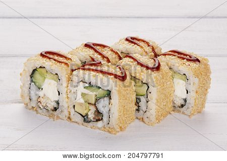 Set of eight rolls with eel sesame avocado and philadelphia cheese decorated with wasabi and ginger on a wooden white background Sushi and chopsticks