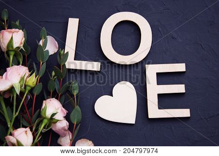 Love letters and pink rose flowers wooden blue background, top view
