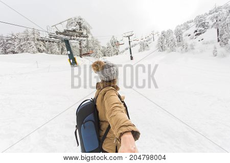 Follow me in ski resort. Young woman holding man by hand going to winter nature in mountains