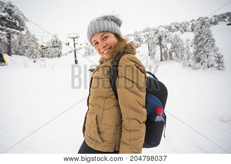 Happy traveler woman with a backpack in winter time.