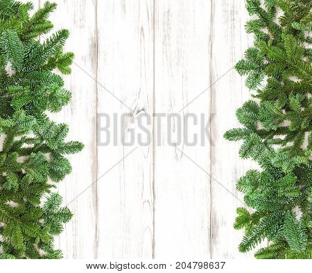 Christmas tree branches on wooden background. Winter holidays decoration