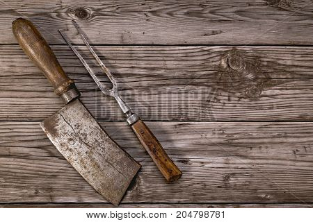 Rustic table with vintage meat cleaver and fork on wooden background with copy space