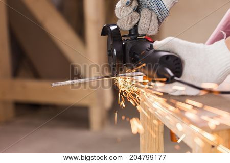 Heavy industry worker cutting steel with angle grinder at car service