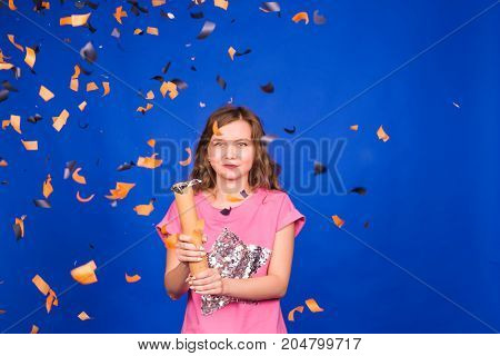 Party time. Cheerful young happy woman or teen girl with confetti.