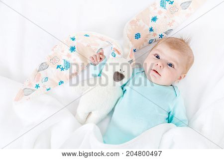 Close-up of adorable cute newborn baby girl of two months on white background. Lovely child playing with plush rabbit toy wigh bit long ears. Holiday, Easter, childhood concept.