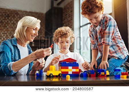 My grandkids are my treasures. Selective focus on a concentrated boy wearing a white shirt and a happy senior woman grinning broadly while sitting next to her grandsons and playing with them at home.