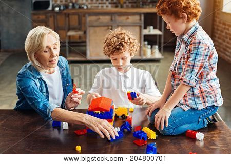 What should we add here. Focused elderly lady and her grandchildren chatting about the house they building while all sitting at a table and playing with a construction set.