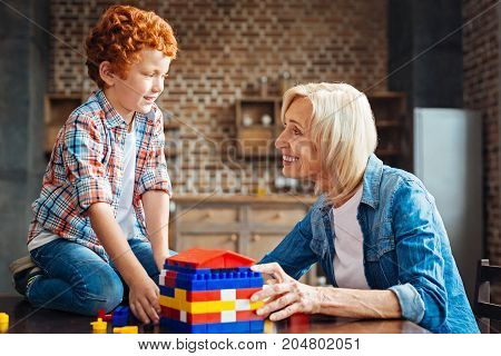 Do you like. Side view on a cheerful senior lady smiling and looking at her curly haired grandson with eyes full of love after playing with a construction set and building a dream house.