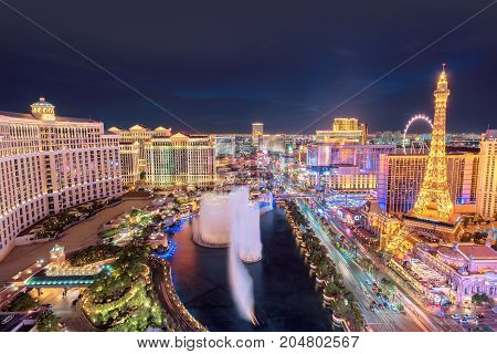 Bellagio Fountains Show and hotels on Las Vegas strip at night on July 25, 2017 in Las Vegas, USA.