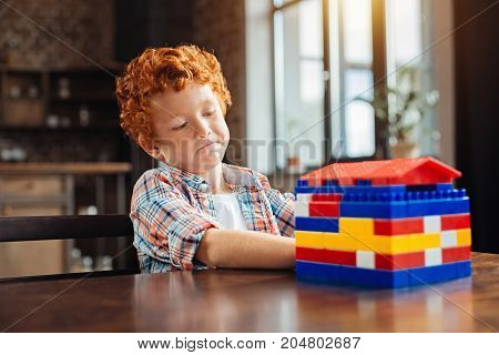 Let me think. Selective focus on a pensive little child looking a built house attentively and thinking of it after playing with a construction set.