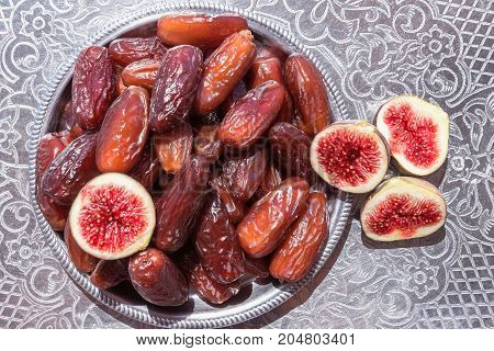 Dried dates in a silver bowl. Exotic fruit.