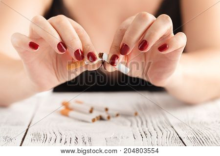Woman breaks down the cigarette by hand.
