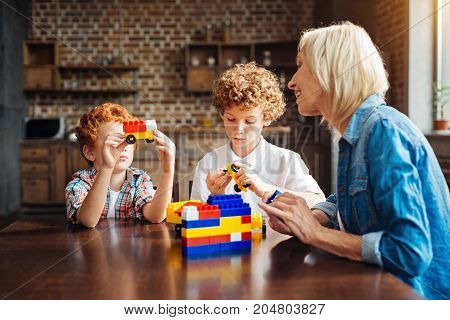 Do you like my car. Selective focus on a curly haired brothers sitting next to each other and getting creative while playing with a construction set together with their careful grandmother.