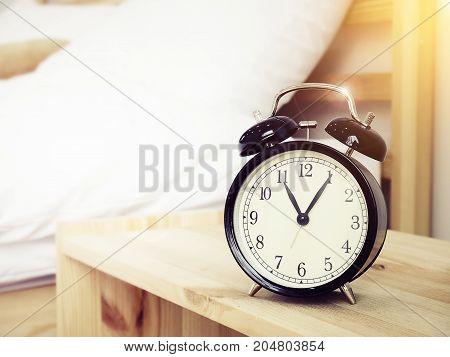 Closeup retro alarm clock on Bedside table with bed background and copy space retro style