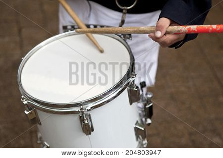 Playing white drums on a marching band