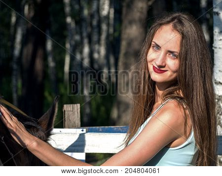 Young lady stroking a horse and smiling in a frame. Summer sunny day.