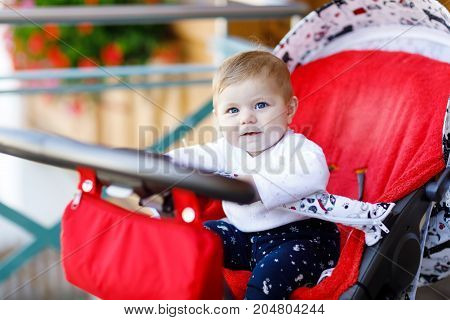 Cute little beautiful baby girl of 6 months sitting in the pram or stroller and waiting for mom. Happy smiling child with blue eyes.