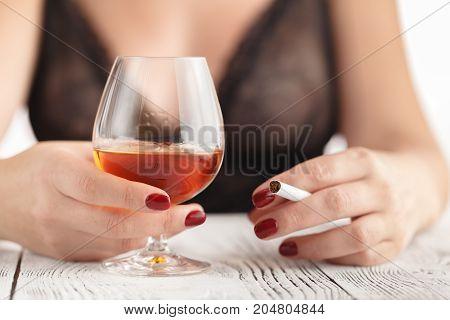 Beautiful woman drinking glass of half cognac.