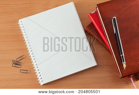 Pen and notebook on a wooden table