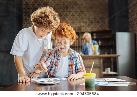 Harmonious atmosphere. Waist up shot of two adorable curly haired children standing close to each other and painting at a table while their mindful grandmother watching them in the background.