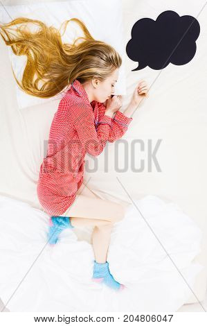 Young Woman Lying On Bed Wearing Pajamas